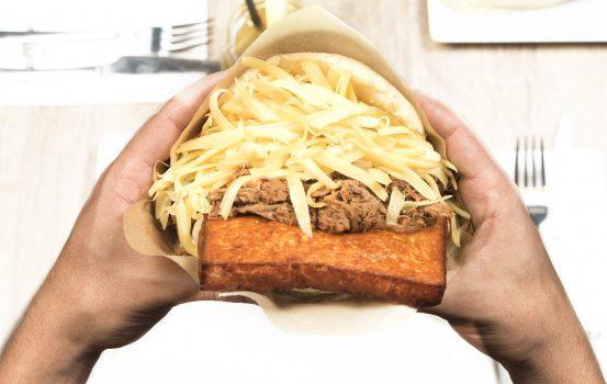 Arepa de queso frito con carne mechada, nata y queso amarillo